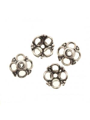 Coppetta tonda con quattro petali forati e decoro a palline tra i petali, diametro 13 mm.