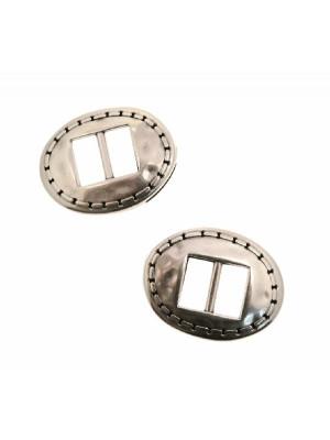 Chiusura per cordoncini o nastri piatti, effetto fibbia, forma ovale con decoro nel contorno, 32x25 mm.
